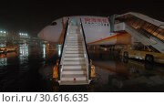 Купить «Aircraft of Hainan Airlines with stairs at rainy night», видеоролик № 30616635, снято 31 октября 2017 г. (c) Данил Руденко / Фотобанк Лори