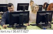 Купить «Group of cheerful modern elderly people working together on computer during pc class», видеоролик № 30617027, снято 26 февраля 2019 г. (c) Яков Филимонов / Фотобанк Лори