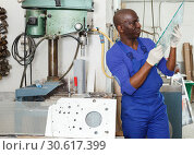 Купить «Serious man working on glass drilling machine», фото № 30617399, снято 16 мая 2018 г. (c) Яков Филимонов / Фотобанк Лори