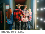 Teenagers with popcorn stands in cinema hall. Стоковое фото, фотограф Tryapitsyn Sergiy / Фотобанк Лори