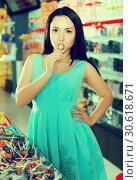 Young woman suck lollipop at candy shop. Стоковое фото, фотограф Яков Филимонов / Фотобанк Лори