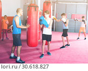 Купить «Boxing instructor helps children learn techniques of strikes», фото № 30618827, снято 12 апреля 2017 г. (c) Яков Филимонов / Фотобанк Лори