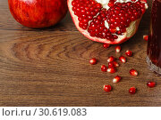Red pomegranate fruits, seeds and glass with juice on a dark surface. Стоковое фото, фотограф Евгений Харитонов / Фотобанк Лори