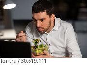 Купить «businessman with computer eating at night office», фото № 30619111, снято 25 января 2019 г. (c) Syda Productions / Фотобанк Лори