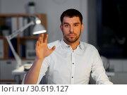 Купить «businessman using gestures at night office», фото № 30619127, снято 25 января 2019 г. (c) Syda Productions / Фотобанк Лори