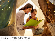 Купить «happy family reading book in kids tent at home», фото № 30619219, снято 27 января 2018 г. (c) Syda Productions / Фотобанк Лори