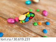 Купить «chocolate egg and candy drops on wooden table», фото № 30619231, снято 15 марта 2018 г. (c) Syda Productions / Фотобанк Лори
