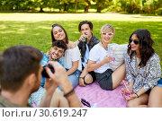 Купить «friends with drinks photographing at summer picnic», фото № 30619247, снято 17 июня 2018 г. (c) Syda Productions / Фотобанк Лори