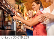 Купить «happy women pouring wine from dispenser at bar», фото № 30619259, снято 25 июня 2018 г. (c) Syda Productions / Фотобанк Лори