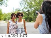 Купить «woman photographing her friends in summer park», фото № 30619275, снято 22 июля 2018 г. (c) Syda Productions / Фотобанк Лори