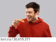 Купить «happy young man eating pizza», фото № 30619371, снято 3 февраля 2019 г. (c) Syda Productions / Фотобанк Лори