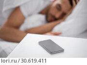 Купить «smartphone on bedside table near sleeping man», фото № 30619411, снято 6 мая 2017 г. (c) Syda Productions / Фотобанк Лори