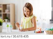 Купить «happy girl coloring easter eggs at home», фото № 30619435, снято 25 июля 2018 г. (c) Syda Productions / Фотобанк Лори