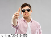 Купить «young man in sunglasses making hand gun gesture», фото № 30619455, снято 3 февраля 2019 г. (c) Syda Productions / Фотобанк Лори
