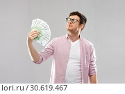 Купить «proud young man in glasses with fan of euro money», фото № 30619467, снято 3 февраля 2019 г. (c) Syda Productions / Фотобанк Лори