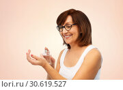 Купить «smiling senior woman spraying perfume to her wrist», фото № 30619527, снято 8 февраля 2019 г. (c) Syda Productions / Фотобанк Лори