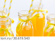 Купить «orange juice in glass bottles with paper straws», фото № 30619543, снято 6 июля 2018 г. (c) Syda Productions / Фотобанк Лори