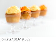 Купить «cupcakes with frosting on confectionery stands», фото № 30619555, снято 6 июля 2018 г. (c) Syda Productions / Фотобанк Лори