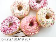 Купить «close up of glazed donuts on white table», фото № 30619767, снято 6 июля 2018 г. (c) Syda Productions / Фотобанк Лори