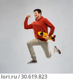 smiling young man in hoodie with short skateboard. Стоковое фото, фотограф Syda Productions / Фотобанк Лори