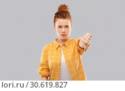 Купить «angry red haired teenage girl showing thumbs down», фото № 30619827, снято 28 февраля 2019 г. (c) Syda Productions / Фотобанк Лори
