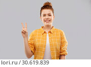 Купить «smiling red haired teenage girl showing peace», фото № 30619839, снято 28 февраля 2019 г. (c) Syda Productions / Фотобанк Лори