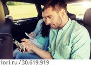 Купить «couple with smartphones riding on back seat of car», фото № 30619919, снято 12 июня 2016 г. (c) Syda Productions / Фотобанк Лори