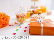 birthday present in orange wrap on table at party. Стоковое фото, фотограф Syda Productions / Фотобанк Лори