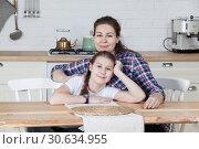 Купить «Мама с дочкой на кухне сидят за столом», фото № 30634955, снято 17 февраля 2019 г. (c) Кекяляйнен Андрей / Фотобанк Лори