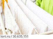 Купить «White and colored linen and towels to be dried on the clothesline», фото № 30635151, снято 2 октября 2018 г. (c) Tetiana Chugunova / Фотобанк Лори