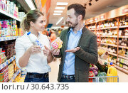 Купить «Couple is looking on shelves with variety products in the supermarket.», фото № 30643735, снято 4 апреля 2018 г. (c) Яков Филимонов / Фотобанк Лори