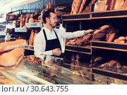 Купить «Seller offering fresh loaf of bread», фото № 30643755, снято 26 января 2017 г. (c) Яков Филимонов / Фотобанк Лори