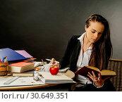 Beautiful teacher sitting at her desk reading. Стоковое фото, фотограф sumners / easy Fotostock / Фотобанк Лори