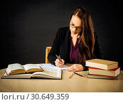 Attractive teacher sitting at her desk writing. Стоковое фото, фотограф sumners / easy Fotostock / Фотобанк Лори
