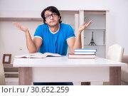 Купить «Young handsome student studying at home», фото № 30652259, снято 31 октября 2018 г. (c) Elnur / Фотобанк Лори