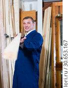 Купить «workman standing with wooden plank», фото № 30653167, снято 21 ноября 2019 г. (c) Яков Филимонов / Фотобанк Лори