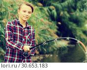 Smiling boy casting line for fishing on lake. Стоковое фото, фотограф Яков Филимонов / Фотобанк Лори