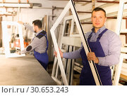 Купить «attentive male professional labours with finished PVC profiles and windows», фото № 30653243, снято 30 марта 2017 г. (c) Яков Филимонов / Фотобанк Лори