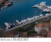 Купить «Aerial view of boats moored at port seen from the way to Kotor Fortress, Kotor, Bay of Kotor, Montenegro», фото № 30653567, снято 20 июля 2019 г. (c) Ingram Publishing / Фотобанк Лори