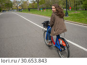 Купить «Happy woman riding a bicycle on road, Central Park, Manhattan, New York City, New York State, USA», фото № 30653843, снято 28 апреля 2016 г. (c) Ingram Publishing / Фотобанк Лори
