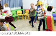 Купить «Happy laughing pupils of primary school having fun during festive event with their female teacher, amusing with colored balloons», видеоролик № 30664543, снято 30 января 2019 г. (c) Яков Филимонов / Фотобанк Лори