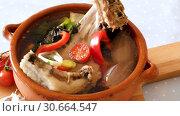 Купить «Soup of lamb with vegetables, lemon, onion and greens, served in bowl», видеоролик № 30664547, снято 28 августа 2018 г. (c) Яков Филимонов / Фотобанк Лори