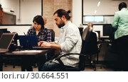 Купить «Focused bearded freelancer concentrated on work with laptop in coworking space with international team», видеоролик № 30664551, снято 12 апреля 2019 г. (c) Яков Филимонов / Фотобанк Лори