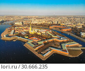 Beautifull aerial view of the Petropavlovsky fortress in sunny spring day. Golden tall spire of famous Peter and Paul Cathedral on the blue sky background. Historical centre of St. Petersburg, Russia. (2019 год). Стоковое фото, фотограф Алексей Ширманов / Фотобанк Лори