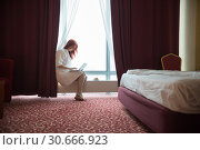 A ginger woman sitting on the window sill in the hotel room. Стоковое фото, фотограф Константин Шишкин / Фотобанк Лори
