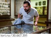 Купить «Attentive adult man exploring artworks in glass case in museum», фото № 30667391, снято 7 апреля 2019 г. (c) Яков Филимонов / Фотобанк Лори