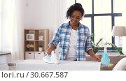 Купить «african american woman ironing bed linen at home», видеоролик № 30667587, снято 15 апреля 2019 г. (c) Syda Productions / Фотобанк Лори