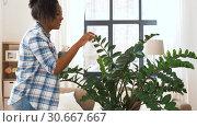 Купить «happy woman cleaning houseplant at home», видеоролик № 30667667, снято 15 апреля 2019 г. (c) Syda Productions / Фотобанк Лори