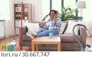 Купить «woman in headphones resting after home cleaning», видеоролик № 30667747, снято 15 апреля 2019 г. (c) Syda Productions / Фотобанк Лори