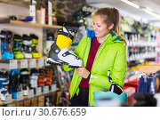 Купить «Buyer woman in red sweatshirt is trying on stylish boots which she choose for skiing.», фото № 30676659, снято 31 июля 2017 г. (c) Яков Филимонов / Фотобанк Лори